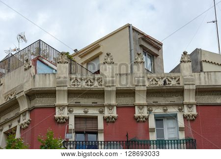 Upper Part Of Old Building Is In Barcelona, Catalonia, Spain.