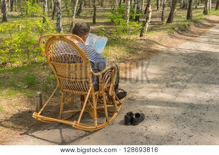 Senior man is having rest in coniferous forest sitting on a wicker rocking-chair and examining map