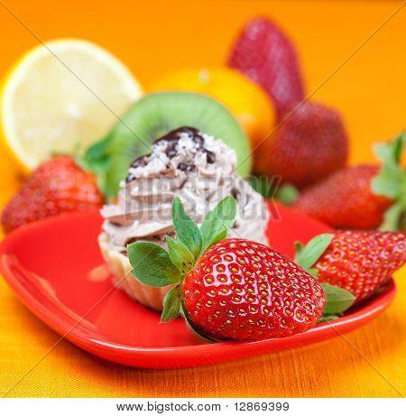 Lemon,mandarin,kiwi,cake And Strawberries Lying On The Orange Fabric