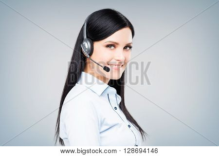 Side portrait of attractive brunette call center operator with headset