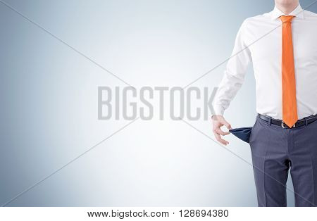 Unemployment concept with businessman showing empty pocket on light grey background. Mock up