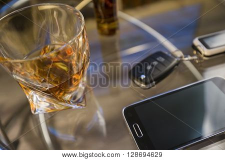 Glass of alcoholic drink and car key, on the table, on light background ** Note: Soft Focus at 100%, best at smaller sizes