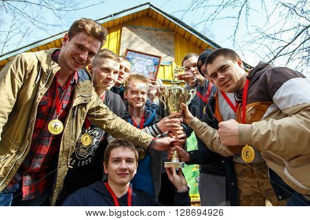 Saint-Petersburg, Russia - April 24, 2016: Paintball tournament in Snaker club between student teams from five universities. Group photo with golden cup.