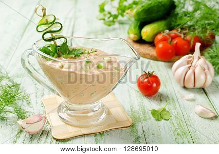 Fresh tomato sauce for meat on a wooden table. Sauce made from fresh tomatoes cucumber mayonnaise paprika garlic herbs and hot peppers
