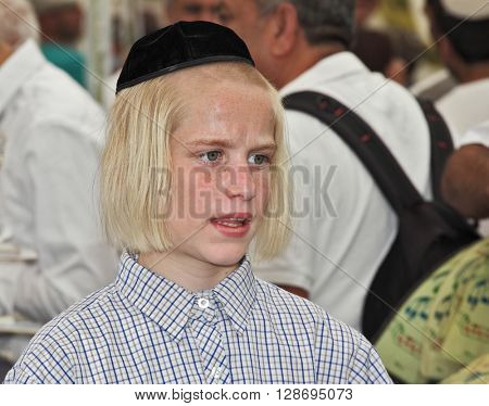JERUSALEM, ISRAEL - SEPTEMBER 18, 2013: Big market on the eve of the Jewish holiday of Sukkot. The boy - teenager with long blond hair and a black velvet skullcap