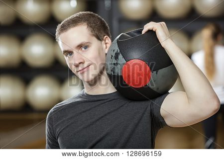 Man Keeping Medicine Ball On Shoulder In Gymnasium