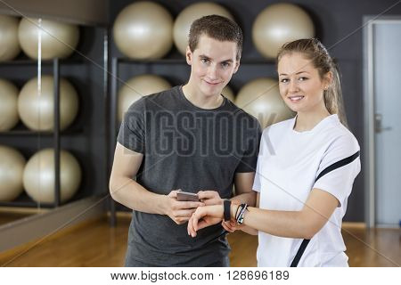 Young Friends Using Smart Phone And Pedometer In Gym