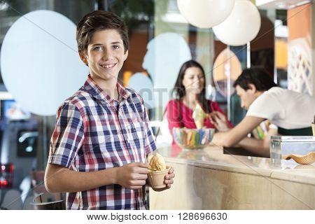 Preteen Happy Boy Having Ice Cream At Parlor