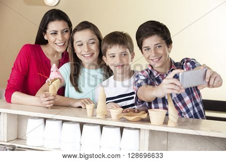 Boy Taking Selfie With Family At Ice Cream Parlor