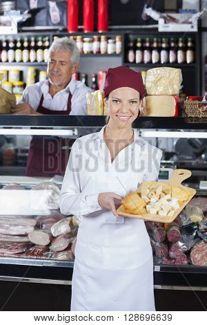 Happy Saleswoman Holding Various Cheese On Board In Store