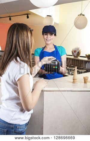 Girl Making NFC Payment On Mobile Phone While Waitress Smiling