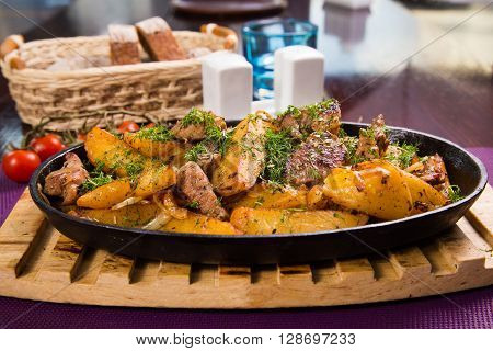 pan with fresh hot meat, potatoes and green dill in restaurant
