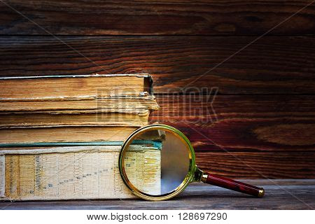 a pile of old books and magnifier on wooden background. the concept of the research the study. with space for text