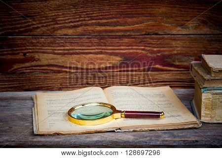 open old book with a magnifying glass and a stack of books on a wooden table. the concept of the study the study. with space for text