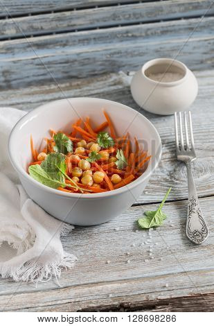 Fresh carrot and chickpea salad on a light wooden background. Healthy vegetarian food