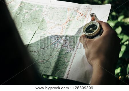 Traveler Exploring Map With Compass In Sunny Forest In The Mountains