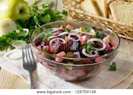 Salad With Apple, Herring And Beetroot, Filled With Vegetable Oil On A Wooden Table.