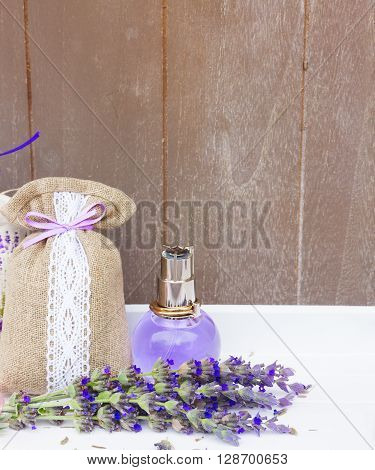 Lavender herbal  water, fresh flowers and dry in pouch, copy space on gray wooden background