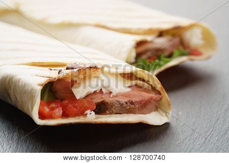 burritos with beef steak, corn, black beans on slate board, vintage toned