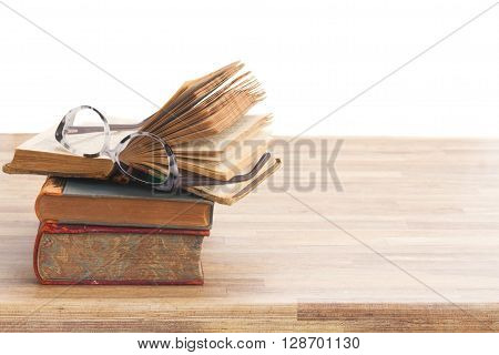 Stack of Books and glasses on wooden table desktop border isolated on white background