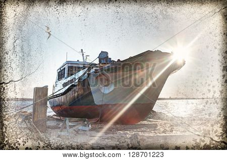 Deserted rusty ship on the coast of the sea.