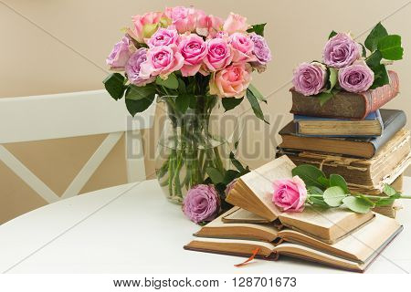Pile of old books with bouqet of  rose flowers