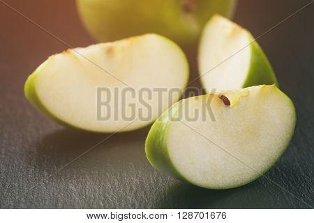ripe green apples sliced on slate board, vintage toned