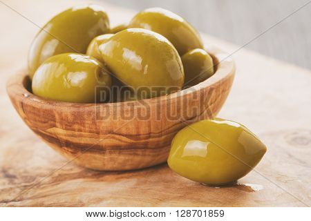 salted giant green olives in olive bowl on wooden table, vintage toned