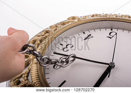 chain tied to minute hand of a clock and pulled on a white background
