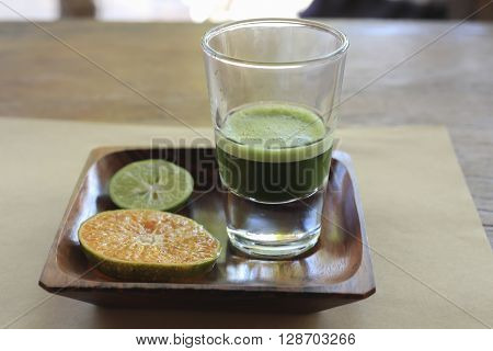 weight grass healthy juice in a glass on a tray with a slice of lemon and orange