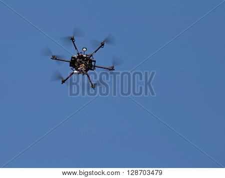 Black quadrocopter, with six rotating propellers, flying in the blue sky, and produces professional video shooting