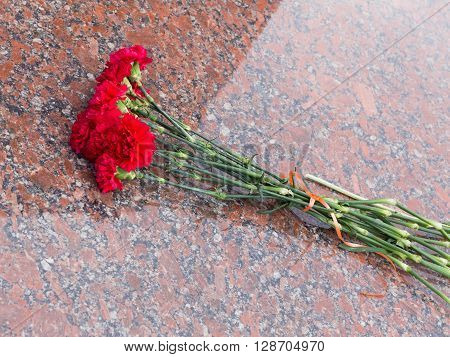 a lot of red carnations on a glossy red granite stone in the day of mourning