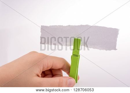 Piece of torn paper clipped with a green clothespin on a white background
