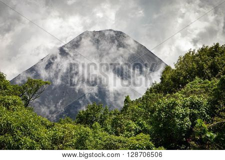 The perfect peak of the active and young Izalco volcano seen from a view point in Cerro Verde National Park in El Salvador covered with thick white clouds