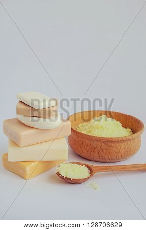 Spa setting with different kind of natural soaps and sea salt in wooden bowl on white background. Tower stack of different handmade soaps on white. Selective focus. Place for text. Copy space.