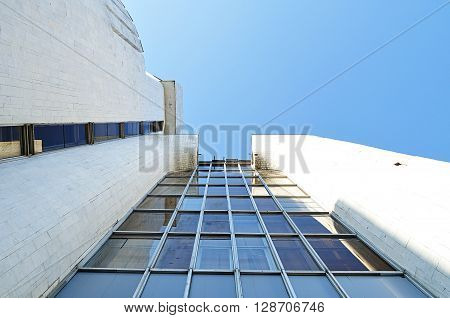 Architecture urban background - perspective bottom view of high building of modern futuristic design. Modern architecture cityscape.