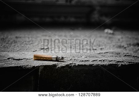 Cigarette butt on the stone steps .