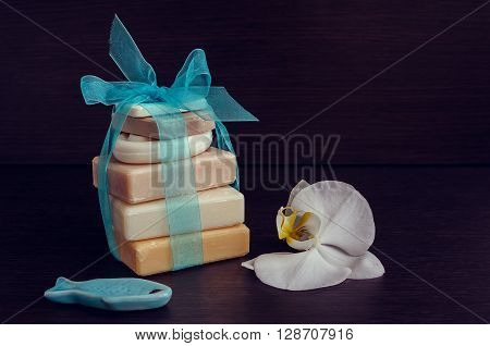 Spa setting in purple and blue colors with different kind of natural soaps and orchid on dark wooden background. Tower stack of different handmade soaps. Selective focus. Copy space.