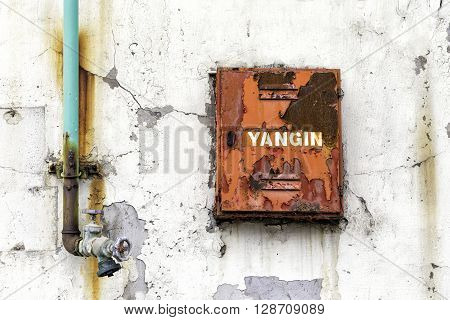 Fire fighter box for fire hose and water valve on an weathered wall of the old building. Yangin means fire in Turkish.