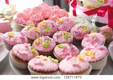 luxury delicious pink cupcakes and candy bar at celebration party in a restaurant