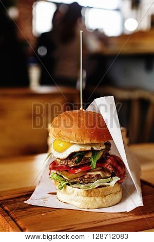 Very Big Juicy Burger With Vegetables Meat Cutlet And Egg On Wooden Background, Space For Text