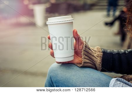 Coffee to go. Woman drinking coffe on the street. Close up ** Note: Visible grain at 100%, best at smaller sizes