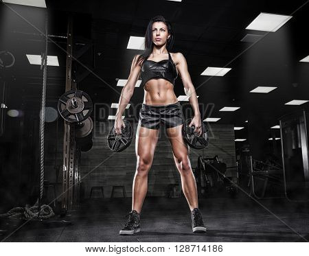 Nice sexy woman doing workout with big dumbbell