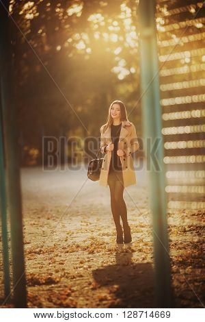 Beautiful young girl in coat in autumn garden