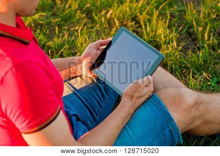 Young man using tablet computer on summer park. Man working on his tablet outdoors in the park. Modern man using tablet pc outside on a park bench.