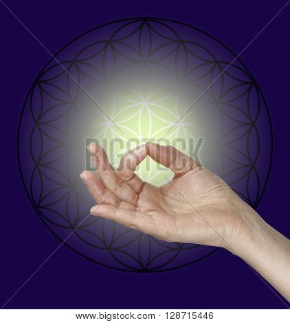 Gyan Mudra and the Flower of Life Symbol - female hand making Gyan Mudra hand position with the Flow of Life symbol in the background and a pale lemon glow surrounded by dark blue