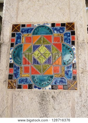 Colorful ceramic Mexican tile displayed in a stone column in an exterior bus station in San Antonio, Texas