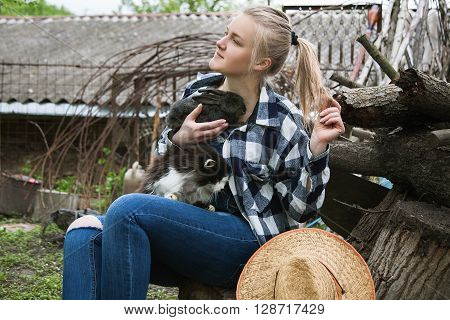 yong blond girl sitting in the village yard dreaming and holding a rabbit in her hands on her lap sitting cat