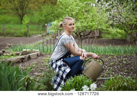 yong blond woman sitting and watering vegetable garden