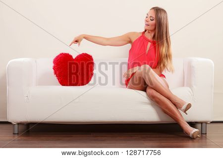 Pretty cute young woman girl with red heart shape pillow sitting on white sofa couch. Valentines day love.